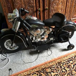 Batteridreven motorcykel til den mindste.  Har bare stået til pynt og aldrig været kørt på. Batteriet virker perfekt og den er ladet op.   Med lys på og knap til båthorn.