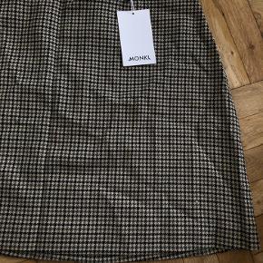 Helt ny nederdel i grøn, sort og beige mønster. Aldrig brugt.