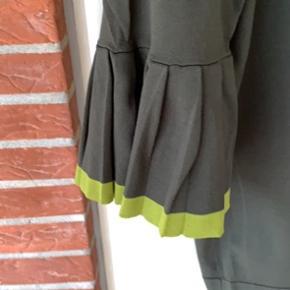 Fin bluse ned 3/4 ærme med fin detalje, flæse i limegrøn. Meget lidt brugt. Kvaliteten lidt tung falder pænt.