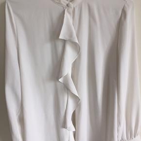 Sød skjorte med flæse foran i polyester.