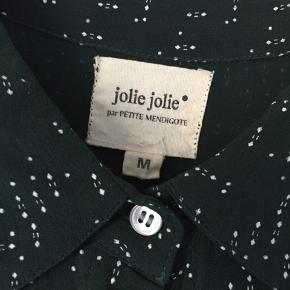 Mørkegrøn kjole med hvidt mønster og sidelommer fra Jolie Jolie. Har knapper på øverste halvdel. Løs model. Måler ca. 90 cm fr skulder til kant.