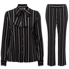 Bukser str. 32 (med elastik i livet) skjorte str. 34.  Materiale 95% polyester 5% viskose.  Bukser: indvendig benlængde 76,5 cm. Fuld længde: 102 cm. Liv: ude at strække 2x 36 cm.  Overdel:  Fra armhule til armhule: 49 cm. Længde fra skulder og ned: 66 cm.  Jakkesæt sæt bukser skjorte bluse.