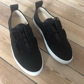 Helt nye gummisko fra By Malene Birger. Modelnavn: Lakana Shoe Black  Nypris: 1899,-  Både æske, skopose og ekstra snørebånd medfølger.  De har kun været oppe af æsken for disse fotos, og sælges da jeg fik et par i læder i stedet.