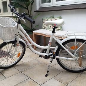 Rigtig fin pigecykel med kurv. Næsten som ny, da den næsten ikke er brugt, har stået i garage. Pludselig er vores pige vokset fra den, og skal have en større cykel ;) Minimum sædehøjde: 65 cm Maximum sædehøjde: ca. 75 cm Pige 6 år, 7 år, 8 år, 6-8 år. Shopper cykel, børnecykel, flettet kurv, 3 gear, håndbremse og med lås.