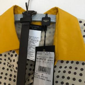 Supertjekket og feminin silke/bomuldskjole (52% silke 48% bomuld) fra Max Mara Weekend. Perfekt forårs/sommerkjole. Råhvid med grå prikker og karrygul krave og kant forneden. Medfølgende mørkebrunt læderbælte. Kjolen har aldrig været brugt. Nypris 1695,- kr. Længde fra skulder til nederste kant: 93 cm