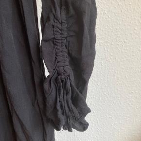 Sort kort kjole med to snore i enden af ærmet der kan strammes eller løsnes.