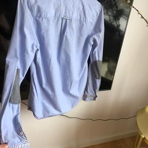 Der er en lille lys plet nederst på skjorten.