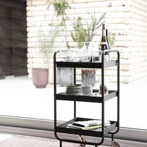 Lækkert og stilrent Roll rullebord i sort stål fra skønne House Doctor.   Når det kommer til rulleborde i indretningen, er de både praktiske og utrolig dekorative, og det fine Roll rullebord er ingen undtagelse. Bordet er fremstillet af stål, som derefter er lakeret i en mat, sort farve, hvilket giver rullebordet et stilfuldt udtryk. Med Roll rullebordet får du et enkelt, stilrent og funktionelt bord og tilmed aftagelig bakke. Derudover er Roll udstyret med hjul, så du kan rulle bordet derhen, hvor du har brug for det. Det smukke Roll-bord omfavner trenden med sit enkle formsprog i rene linjer.   Brug rullebordet i alle husets rum -  i stuen til ekstra opbevaring af eksempelvis magasiner, bøger eller en fin vase, på badeværelset til diverse cremer og håndklæder eller måske som cocktailbord i stuen. Stil morgenkaffen på bakken og server den på sengen herefter - luksuriøst og lækkert!  Kun fantasien sætter grænser med dette smukke rullebord.   Materialer: Roll rullebordet er fremstillet i sort metalstål.   Mål: Højde: 85 cm. Bredde: 38 cm. Længde: 42 cm.  Afhentes i Veksø, Nordsjælland.