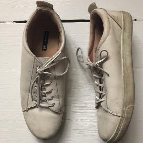 Hvide sneakers i læder fra H&M Premium Quality. Snørrebåndene er også i læder. De er godt brugte, men er ikke gået op nogle steder eller har andre tegn på slid ud over at de er snavsede 😊  Str. 40, men passer også en lille 41