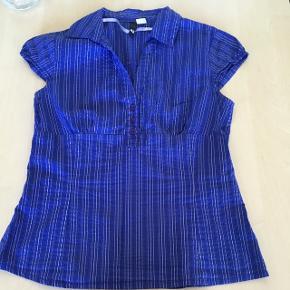 Lilla skjorte med striber i hvid og sølv. På billedet syner den blå, men den er lilla ☀️😊