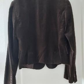 Så smuk mørkebrun blød velour jakke som jeg har brugt en enkelt aften eller to. Jeg er et nummer større nu. Og lidt ærgerlig over at den bare hænger i mit skab. Kun derfor sælges den.. Vaskeanvisningen har jeg klippet af, men jakken må kun renset. Køber betaler for porto, sendes med DAO.