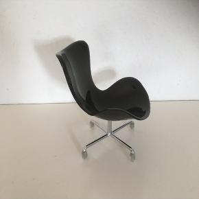 Sort lænestol ligner den kendte designstol fra Arne Jacobsen   Ministol ca 20 cm høj  stol   Smuk pynt på hylde skænk eller reol   Dupperne kan tages af   Fin stand   Sender gerne   Se flere annoncer