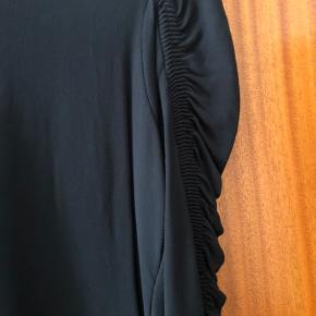 Fin klassisk bluse med rynkeeffekt ved ærmerne.