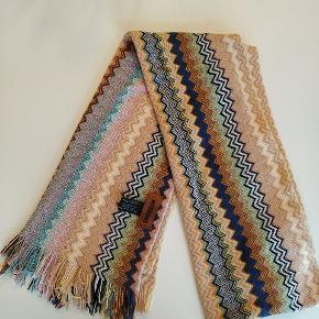 Populært halstørklæde fra Missoni i de lækreste farver. Det har en lille fejl, men det er syet så det ikke kan gå mere op. Se vedlagt billede. Ellers fremstår det som nyt🌸