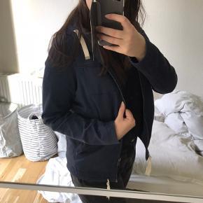 Rigtig dejlig jakke. Selve jakken er ikke som sådan slidt men der er gået hul på den ene lomme og snoren i den anden side har mistet metallet. Ellers i god stand