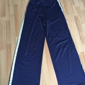 Flotte mørkeblå bukser med kant ved siderne i hvid og guld.