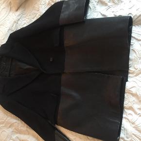Varetype: Skønneste frakke/jakke i cashmere blend med læder besætning Størrelse: 40 itl Farve: Sort Oprindelig købspris: 11000 kr.  Meget smuk frakke/jakke fra det lækre mærke Belstaff. Jakken er i uld/cashmere blanding med læder besætning på ærmer og nederst på jakken. Bemærk jeg har haft jakken på 3 gange men tillader mig at sætte standen til ny! Har stadig tags og ekstra knapper. Jakken ligger i den dyre ende til 1495 euro fra ny! Modellen hedder Benmore Single Breasted Coat Woman 😃 Den måler ca 42 cm over ryg fra skulder til skulder.  Den måler ca 54 cm over ryg fra ærmegab til ærmegab. Tror det er en itl 40 men er ikke sikker - derfor mål 😃