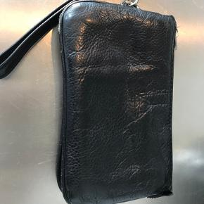 Skind pung med håndleds rem. 17x10 cm. Har desværre fået et hul på nederste kant. Derfor prisen. Se billede.