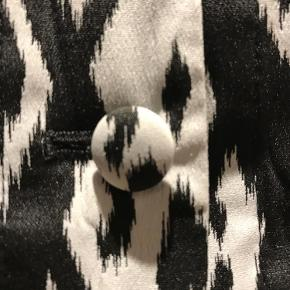 EKSTRA NEDSAT!!! Super flot tunika / lang vest i sort-hvid med grafisk mønster. Kina krave, stofbetrukket knapper og 2 lommer.   Kan bruges både med eller uden en kort- eller langærmet top under.   Mål:  Bryst ca. 96  Talje ca. 84  Længde ca. 80  Super flot tunika / vest Farve: Sort Hvid Oprindelig købspris: 1300 kr.
