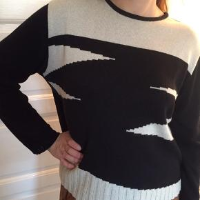 Sort lækker sweater i 50% bomuld, 50% akryl, med mønster foran i beige.
