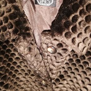 Super lækker mørkebrun faux fur jakke fra Kello. Str 46. Lommer foran. Lukkes med knapper. Pelsen ligger lidt ned et sted på ryggen. Har taget et billede af det med blitz. Det betyder ingenting. Har derfor sat den i kategorien god men brugt. 150,- pp og mobilepay Sender hurtigt