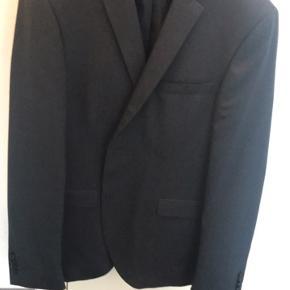 """Sælger dette mørkeblå jakkesæt. Mærket hedder """"premium"""" og er Jack & Jones' eget mærke.  Jakken er str. 52, mens bukserne er str. 98 Nyprisen var omkring 2000, og det er blevet brugt én gang til en konfirmation, så det er derfor som nyt.  750,-"""