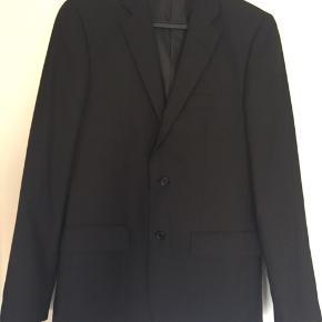 Flot sort 2-knaps jakkesæt - kun brugt 1 gang. Sættet er fint og 100% i orden. Jakke har 2 lommer samt slids midt bag. Bredde - målt under ærmegab er ca 48 cm - Lgd midt bag er ca 76 cm. Buks - skridtlængde ca 76 cm/ livvidde ca 90 cm.