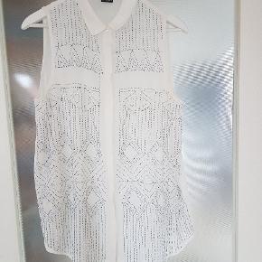 Feminin hvid skjorte med perlemønster foran. Den er rigtig god til at peppe et outfit lidt op.  Skjorten er gennemsigtig og lidt tung på grund af perlerne.