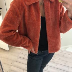 Blød og bamset jakke i orange/fersken farvet.