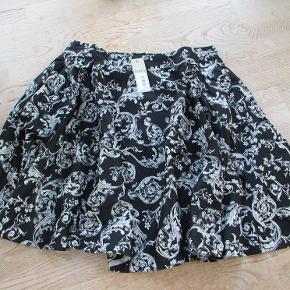 Damaskprintet Nederdel i mørkeblå med hvidt mønster. Nederdelen lukkes bagpå med knap og lynlås, der er elastik i begge sider. Der er mørkeblåt indefoer, der hindrer den er gennemsigtig. Materiale: 97% bomuld 3% elastan Hel længde: Ca 55 cm. Jeg har også nederdelen i str 50 #30dayssellout Se også mine flere end 100 andre annoncer med dame-herre-børne og fodtøj
