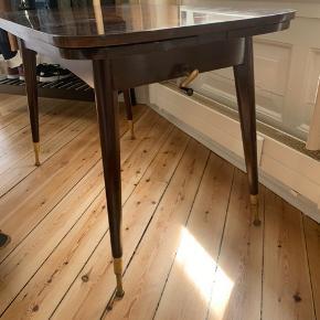 Sælger dette antikke bord fra 60'erne grundet flytning. Det stammer fra Tyskland (Berlin). Bordbenene er af messing. Bordet kan justeres i højde med et håndtag der også er af messing. Det kan også slåes ud, så der kan sidde flere omkring bordet og der bliver mere plads til mad. Mål: L: 110 B: 65, 114 når det er slået ud. H: 74 (kan justeres efter behov)