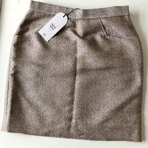 """Den fineste korte nederdel i """"guld"""", der blinker let alt efter lyset 🌟 Størrelse 34/S.  Aldrig brugt - kun prøvet på.  Behagelig foret med bomuld og pink detaljer.  Talje: ca 2 x 37 cm Længde: 47 cm  Se også mine andre annoncer og gør en god handel. 🎶"""