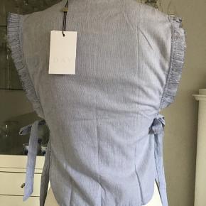 Sød stribet top, der er åben/bindes i siderne. Den er derfor også fleksibel i str. Læg og knapper foran. Flæser på ærmegab med rå kant.