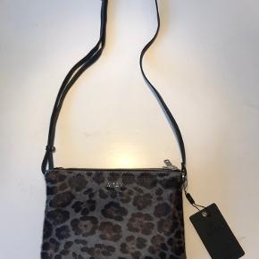 Adax taske i sort læder, med 'leopard pels' på fronten.  Tasken har tre lynlås rum. I det midterste rum er der ligeledes en lynlås lomme og en lomme.  Tasken har en justerbar rem. Tasken er ny. Stadig med mærke. Dustbag medfølger.  ⭐️jeg sender gerne, og ellers kan det afhentes i Farum eller i Fields (Amager) ⭐️