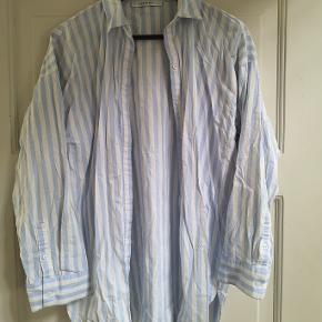 Lyseblå og hvidstribet oversized skjorte. Bomuld.