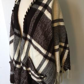 Poncho med hætte. Blød og lækker. Næsten som et tæppe. One size. Den er 76-78cm fra hals/nakke til bund.  Brugt få gange. Men mangler knap.  Vasket på uldprogram.  Sælges for familie.
