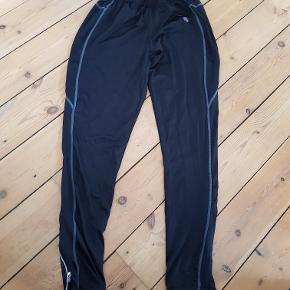 Mærke: Blueman mens functional runningwear  Løbetights med lange ben. Elastik i livet med justerbar snøre indvendigt. Lynlåslukning ved ankler. Lille lynlåslomme bagpå til nøgle mv. 92% polyester/8% elestan.  Brugt få gange