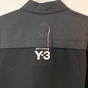OBS! Privatbeskeder og kommentarer besvares som udgangspunkt ikke. Prisen er fast.   Y-3 Adidas x Yohji Yamamoto jakke. Måler 100 cm i længden fortil og 112 cm i længden bagtil.