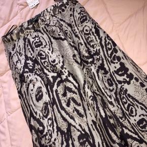 Smuk sølvgrå silkenederdel fra Mng , aldrig brugt.    Prisen er kun 220 inkl. Porto 😃   Tags: Sølv grå sort 36 small mango lang nederdel silke premium mønstret luksus mønster elegant