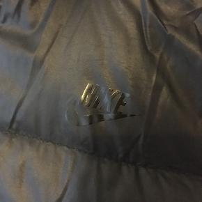 Let dynejakke fra Nike med hætte, som kan lynes af.  Body: 100% nylon. For: 100% polyester. Fyld: Grå gåsedun.