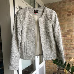 Rigtig fin jakke / blazer / cardigan, som både kan bruges til hverdag og uden over en kjole! Farven er sort/hvid og stoffet er tweed agtigt!