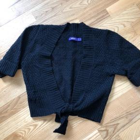 Kort sort cardigan fra Mexx i strikket flet-mønster. Kan bindes på maven. Uld.