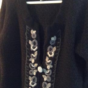Varetype: Kort Farve: sort  Meget flot og lækker cardigan i sort med grå og sølv blomster. Bomber og bred rib ved ærmet. Ærmlængde ca 54 cm, ryg ca 53 cm og længde ca 54 cm
