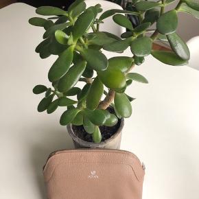 Adax lille lysebrun kosmetik taske med sølv lynlås foroven. Indeni er der et stort rum samt to lommer i hver side. Den ene lomme er med lynlås. Bagpå er der Adax logo med lille søl mønt 🐿 Tasken kan bruges som clutch eller kosmetik taske. Der er ingen stropper på den.   Byd gerne kan både afhentes i Århus C og sendes på købers regning 📮✉️