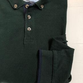 Langærmet polo i en dyb grøn farve med mange detaljer. Kvaliteten er bomulds pique.  OBS! Ønskes handlen gennemført via TS afholder køber gebyret.