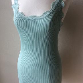 Farve: lys aqua. Materiale: 70% silke, 30% bomuld. Lang top. Perfekt stand. Sendes for kr. 35,-