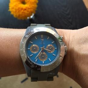 Ældre Triwa ur med blå baggrund og grålig rem.   Uret er af ældre dato og remmen kan trænge til udskiftning eller rens (kan gøres med vatpind etc.) Sælges derfor billigt!    Sendes mod porto.