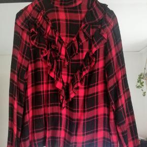 Rødternet skjorte med frynser på brystet. Kun brugt et par gange gange. Smuk og meget behagelig at have på! Sælger da jeg ikke får den brugt. Skriv evt for flere fotos.  75kr