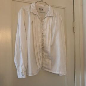 Flot hvis skjorte med fine knapper. Skjorten er en str. 46. Dog lille i størrelsen og kan bruges som oversize.