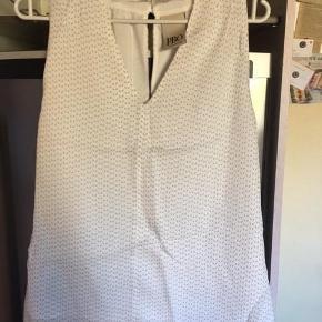 Varetype: Top Farve: Hvid Oprindelig købspris: 899 kr.  Helt ny top i 100% silke - med for af viscose og polyester. Den er let og rigtig sommerlig - skåret lidt ind på skuldrene, og lukkes med knapper i nakken. Er kun prøvet på og desværre købt for lille. Den er hvid med diskret småt mønster i gråt.  Mål over bryst: 51 cm. ( synes den er lidt lille i størrelsen)  Bytter ikke og sender med DAO